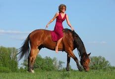 Meisje leggen bareback ontspannen op haar paard Stock Afbeelding