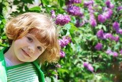 Meisje in lilac tuin Stock Afbeeldingen