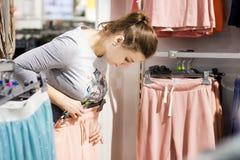 Meisje in manierboutique die op nieuwe modieuze kleren proberen de jonge vrouw koopt kleren in opslag Totale verkoop in wandelgal stock foto's