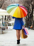 Meisje in mantel met het winkelen zakken en paraplu stock foto