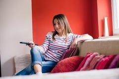 Meisje met afstandsbediening op bank royalty-vrije stock foto's