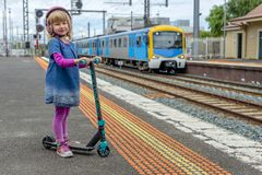 Meisje met autoped bij station 05 stock afbeelding