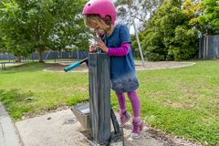 Meisje met autoped drinkwater 03 stock afbeelding