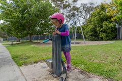 Meisje met autoped drinkwater 04 stock afbeelding