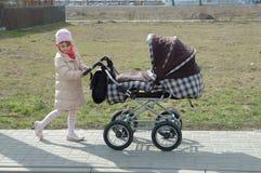 Meisje met babydrager Stock Afbeeldingen