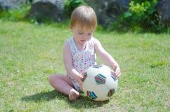 Meisje met bal op gazon Royalty-vrije Stock Afbeeldingen