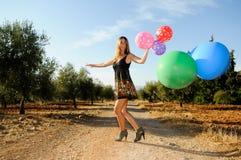Meisje met ballons op het gebied Stock Foto's
