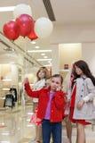 Meisje met ballonstribunes met ledenpoppen in de opslag stock foto