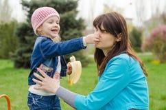 Meisje met banaanmoeder geknepen neus stock afbeelding