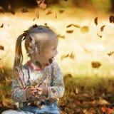Meisje met Benedensyndroom die witte bladeren in de herfstpark spelen Stock Afbeeldingen