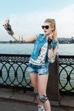 Meisje met beschermingsslijtage die en selfie zich op telefoon bevinden nemen en vredesteken houden Stock Foto