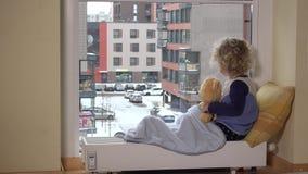 Meisje met beste vriendenteddybeer die de blizzard van de sneeuwdaling door venster bekijken stock footage