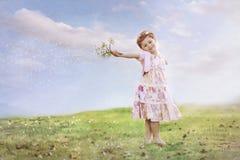 Meisje met bloemen in de blazende wind Royalty-vrije Stock Foto
