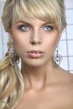 Meisje met blond haar en grote oorringen Stock Foto's