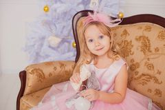 Meisje met blond haar in roze kleding op nieuwe jaarachtergrond stock foto