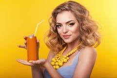 Meisje met blond krullend haar met juweel, die oranje fles van drank houden Royalty-vrije Stock Afbeeldingen