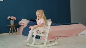 Meisje met blonde haarzitting op een schommelstoel in de ruimte stock videobeelden