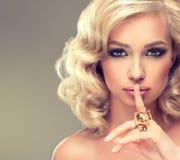 Meisje met blonde krullend haar met grote ringen Royalty-vrije Stock Foto