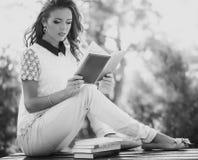 Meisje met boek in de tuin Royalty-vrije Stock Afbeeldingen