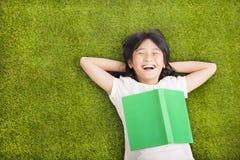 Meisje met boek en het rusten op het gras stock afbeelding