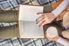 Meisje met boek op benen en koffie ter beschikking royalty-vrije stock foto