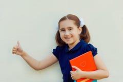 Meisje met boeken tegen de muur stock foto