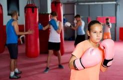 Meisje met bokshandschoenen die in verdedigde houding stellen royalty-vrije stock fotografie