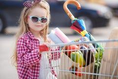 Meisje met boodschappenwagentje met producten Stock Foto's