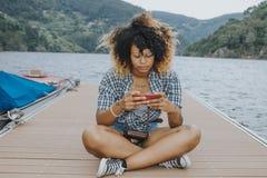 Meisje met cellphone op de pier royalty-vrije stock foto