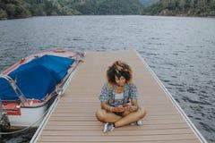Meisje met cellphone op de pier royalty-vrije stock afbeelding