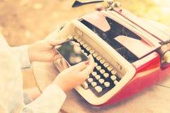 Meisje met celtelefoon en schrijfmachine Royalty-vrije Stock Fotografie