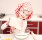 Meisje met chef-kokhoed gezette bloem voor bakselkoekjes Stock Foto's