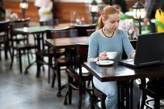 Meisje met computer in koffie Royalty-vrije Stock Foto's