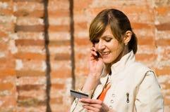 Meisje met creditcard en mobiele telefoon Royalty-vrije Stock Foto's