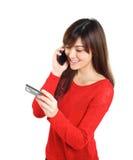 Meisje met creditcard op mobiele telefoon Stock Foto's