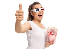 Meisje met 3D glazen en popcorn die duim op gebaar maken Royalty-vrije Stock Afbeelding