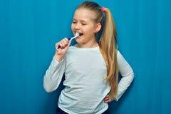 Meisje met de lange schoonmakende tanden van het blondehaar met toothy bru royalty-vrije stock afbeelding