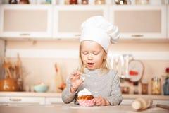 Meisje met de proevende cake van de chef-kokhoed in keuken royalty-vrije stock afbeeldingen