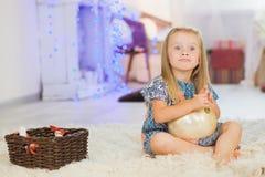 Meisje met de reusachtige bal van de Kerstmisboom Stock Foto