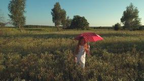 Meisje met de rode hand van paraplugolven en gangen op de weide stock video