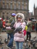 Meisje met duiven op de Dam in Amsterdam royalty-vrije stock foto