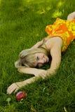 Meisje met een appel op een groen gazon Stock Foto's