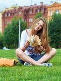 Meisje met een boek in het park stock afbeelding