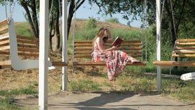 Meisje met een boek op een bank in het park stock video