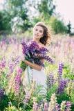 Meisje met een boeket van lupine op het gebied stock foto's