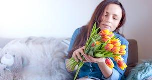Meisje met een boeket van tulbpans op de bank thuis Een gift op Moeder` s Dag Een prettige verrassing Vrouw in de ruimterente royalty-vrije stock afbeelding