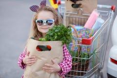 Meisje met een boodschappenwagentjehoogtepunt van kruidenierswinkels dichtbij de auto Royalty-vrije Stock Afbeelding