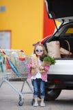 Meisje met een boodschappenwagentjehoogtepunt van kruidenierswinkels dichtbij de auto Stock Foto's
