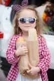Meisje met een boodschappenwagentjehoogtepunt van kruidenierswinkels dichtbij de auto Royalty-vrije Stock Foto
