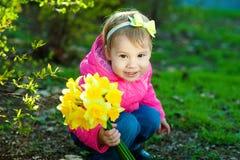 Meisje met een boog op zijn haarzitting op het gras en holding een boeket van gele gele narcissen Een kind loopt buiten binnen royalty-vrije stock afbeeldingen